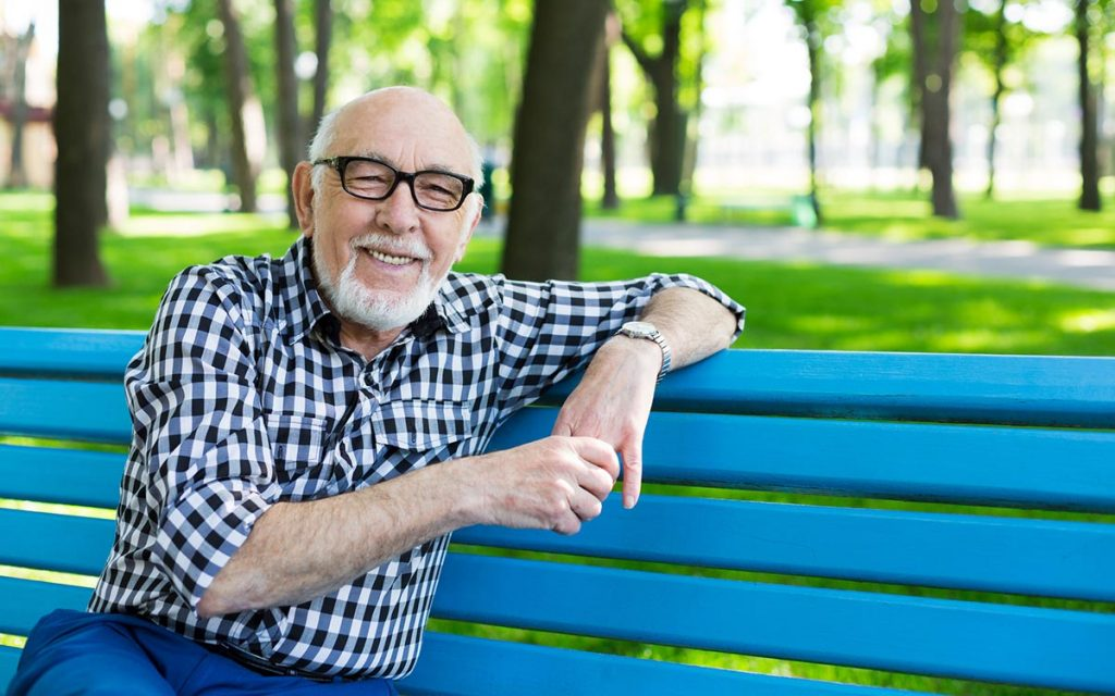 Relaxed senior man outdoors with options about hearing loss.