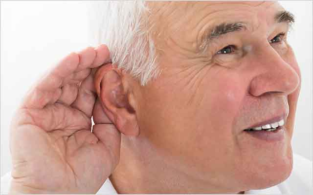 Man with his hand up to his ear experiencing sudden hearing loss in one ear.