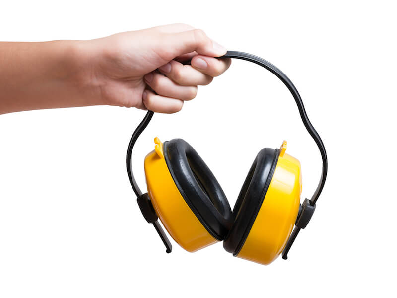 Hand holding hearing protection earmuffs that can prevent hearing loss.