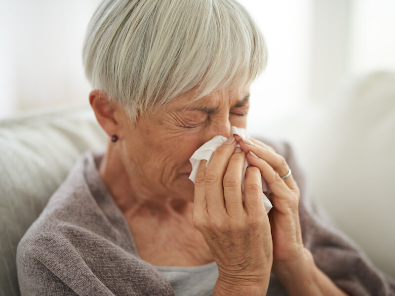 Woman with sinus pain blowing her nose on the couch wondering if it's just a cold or something else.