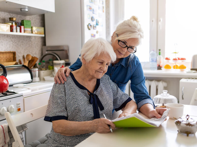 Woman showing her mother information about hearing loss and hearing aids in the kitchen.