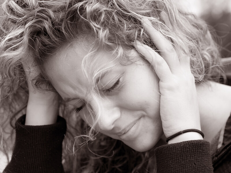 Woman holding her head from ringing in the ears and looking depressed.